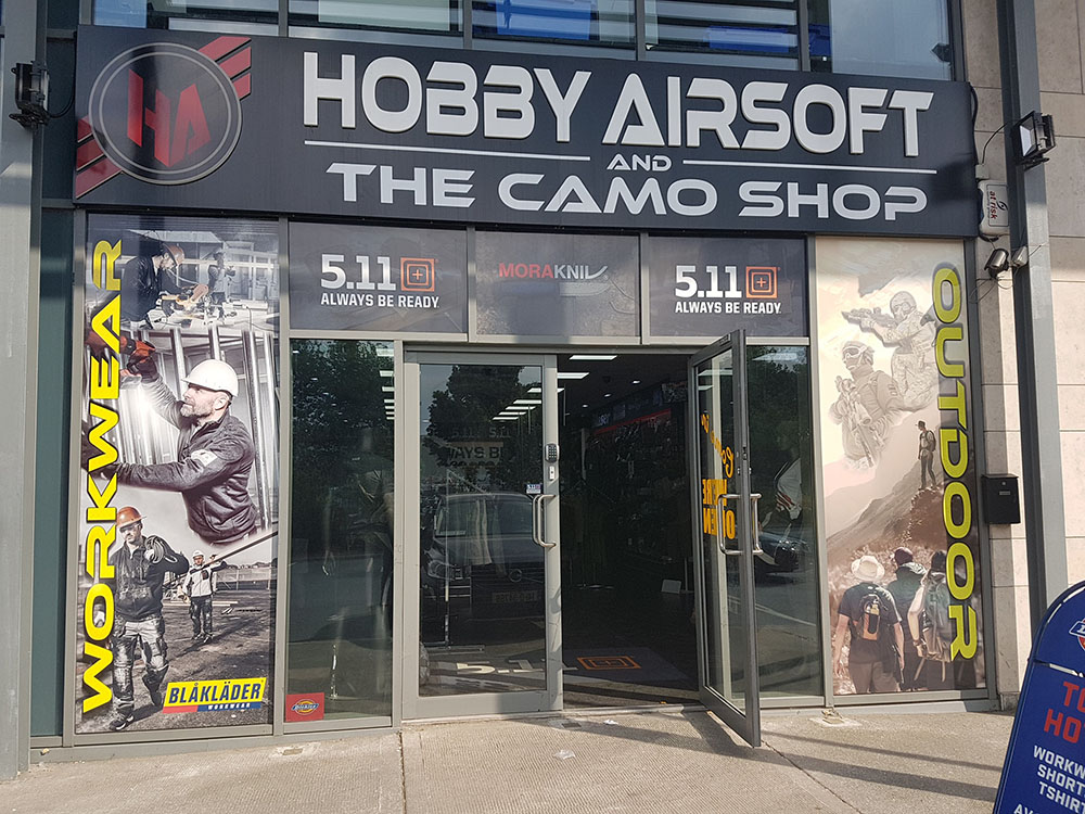 Shop front exterior; large posters showing tactical gear